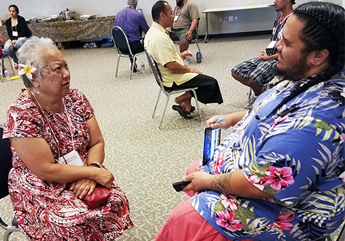 MANA student talking to an elderly pacific islander woman.